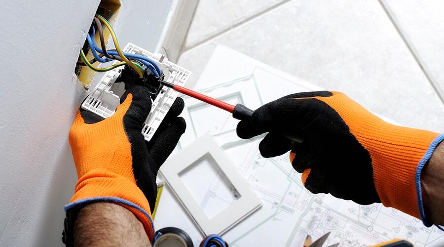 fitting plug socket with orange gloves